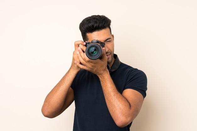 Giovane uomo bello sopra fondo isolato con una macchina fotografica professionale