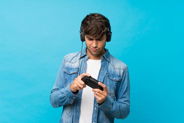 Giovane uomo bello sopra il blu isolato che gioca ai videogiochi