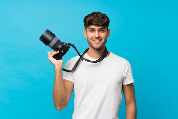 Giovane uomo bello sopra il blu isolato con una macchina fotografica professionale