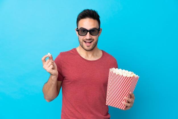 Giovane uomo bello sopra l'azzurro con gli occhiali 3d e in possesso di un grande secchio di popcorn