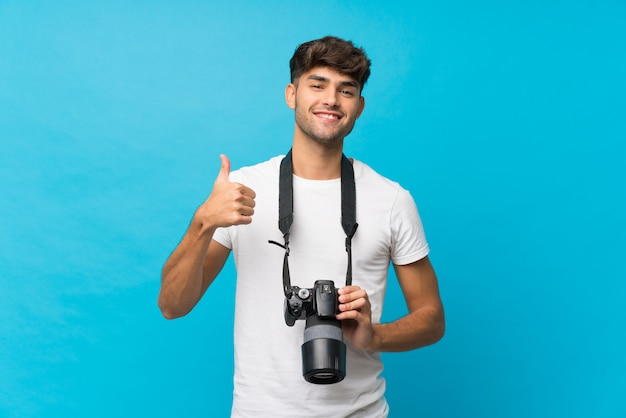 Giovane uomo bello sopra l'azzurro isolato con una macchina fotografica professionale e con il pollice in su
