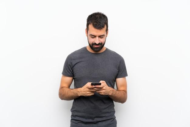 Giovane uomo bello sopra la parete bianca isolata che invia un messaggio con il cellulare