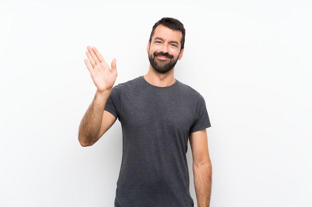 Giovane uomo bello sopra la parete bianca isolata che saluta con la mano con l'espressione felice