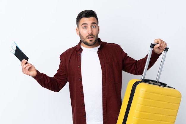 Giovane uomo bello sopra la parete bianca isolata in vacanza con la valigia e passaporto e sorpreso