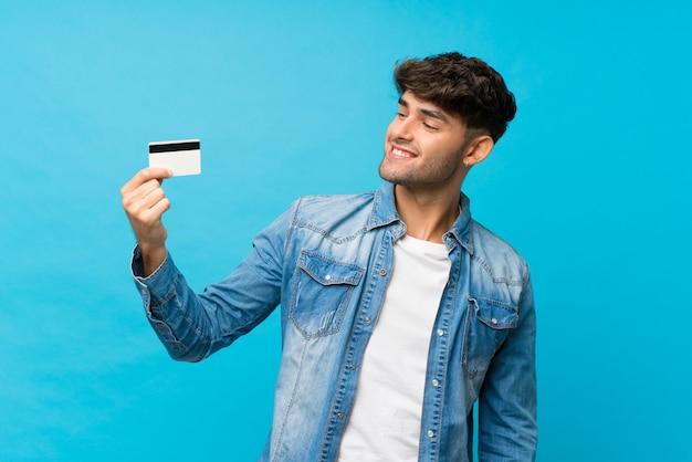 Giovane uomo bello sopra la parete blu isolata che tiene una carta di credito