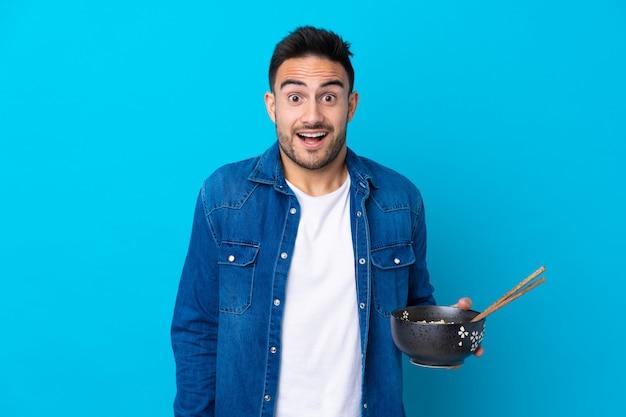 Giovane uomo bello sopra la parete blu isolata con espressione facciale sorpresa e scioccata mentre si tiene una ciotola di noodles con le bacchette