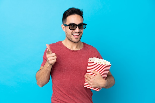 Giovane uomo bello sopra la parete blu isolata con gli occhiali 3d e tenendo un grande secchio di popcorn mentre punta davanti