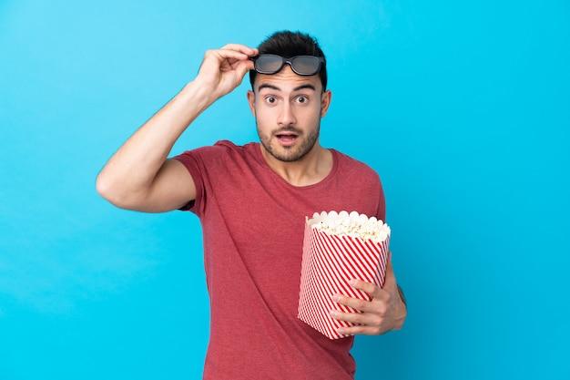 Giovane uomo bello sopra la parete blu isolata sorpresa con gli occhiali 3d e in possesso di un grande secchio di popcorn