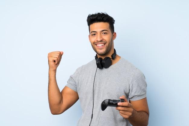 Giovane uomo bello sopra la parete isolata che gioca ai videogiochi
