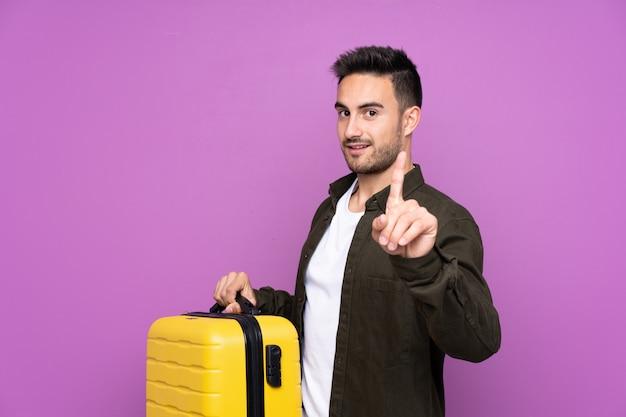 Giovane uomo bello sopra la porpora in vacanza con la valigia di viaggio e contando uno
