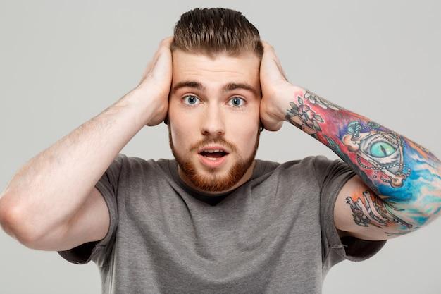 Giovane uomo bello sorpreso che posa sopra la parete grigia.