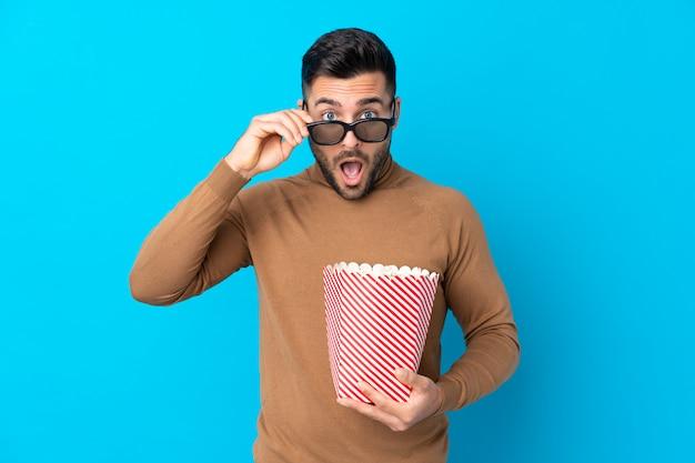 Giovane uomo bello sorpreso con gli occhiali 3d e in possesso di un grande secchio di popcorn