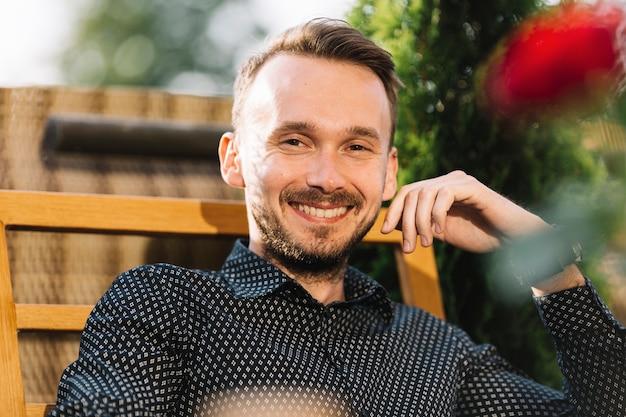Giovane uomo bello sorridente che guarda l'obbiettivo