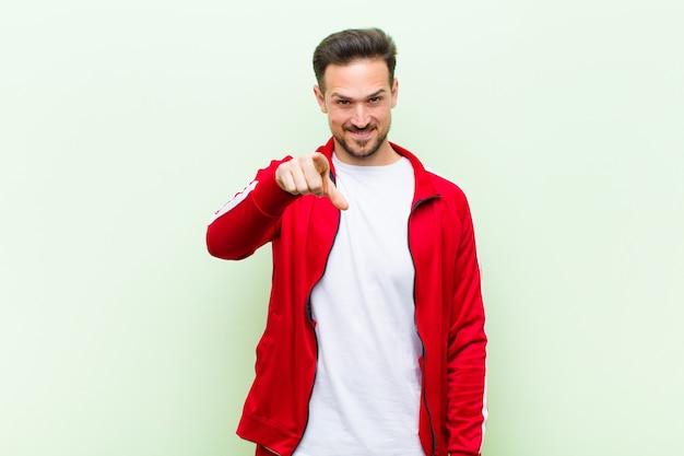 Giovane uomo bello sportivo o monitor che punta alla fotocamera con un sorriso soddisfatto, fiducioso, amichevole, scegliendovi contro la parete piatta