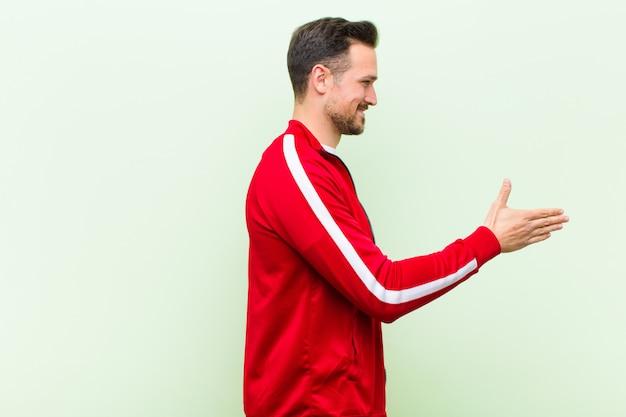 Giovane uomo bello sportivo sorridente, salutandoti e offrendo una stretta di mano per chiudere un affare di successo