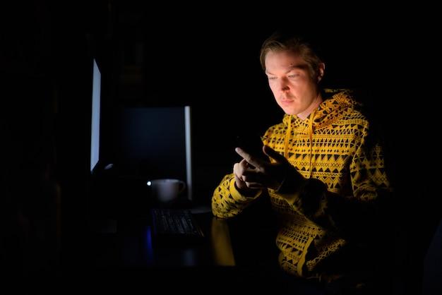 Giovane uomo bello utilizzando il telefono durante il lavoro straordinario a casa al buio