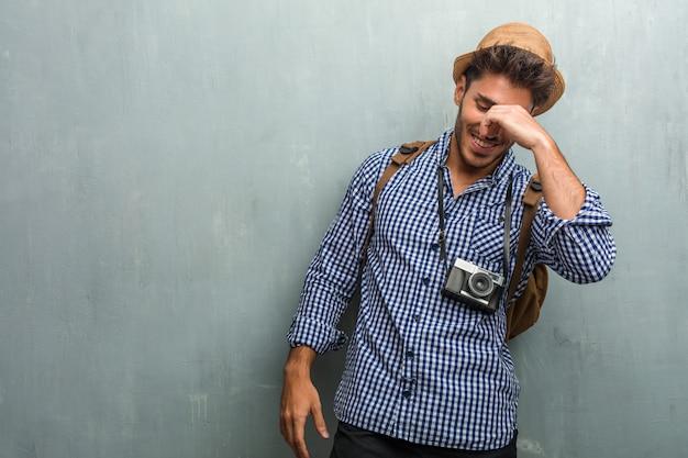 Giovane uomo bello viaggiatore che indossa un cappello di paglia, uno zaino e una macchina fotografica che ride e divertirsi