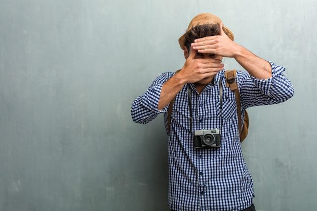 Giovane uomo bello viaggiatore indossa un cappello di paglia, uno zaino e una macchina fotografica guardando attraverso una fessura, nascondendo e socchiudendo gli occhi