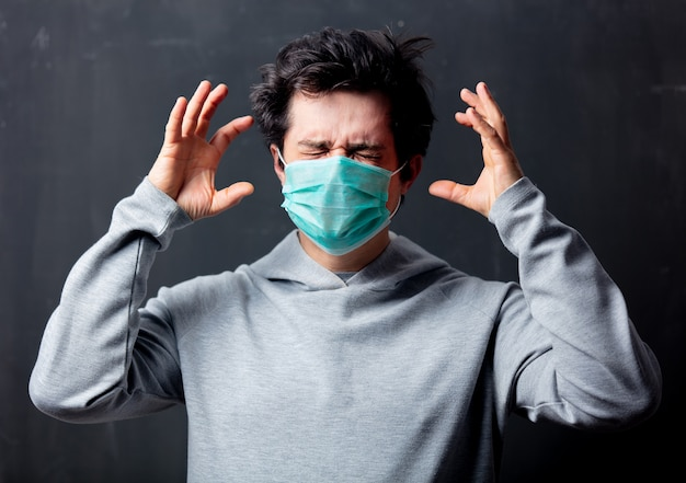 Giovane uomo bianco in maschera protettiva con mal di testa
