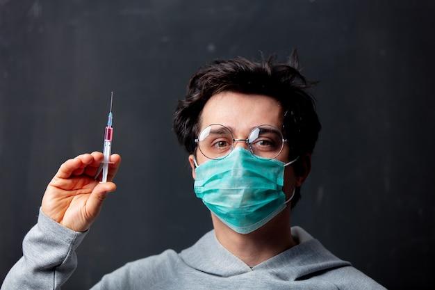 Giovane uomo bianco in maschera protettiva con vaccino a siringa