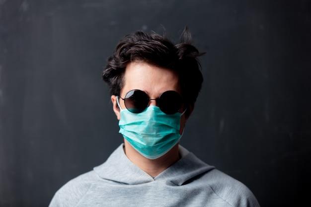 Giovane uomo bianco in maschera protettiva e occhiali da sole