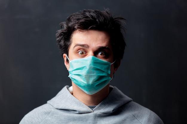 Giovane uomo bianco in maschera protettiva su sfondo scuro