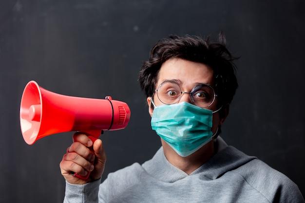 Giovane uomo bianco in occhiali e maschera protettiva con altoparlante