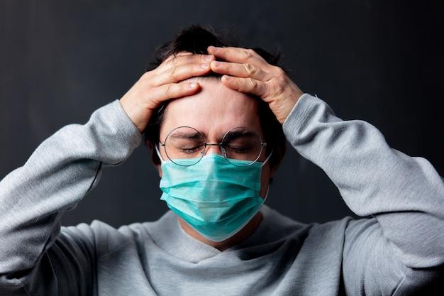 Giovane uomo bianco in occhiali e maschera protettiva con mal di testa
