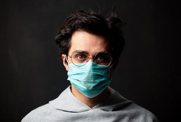Giovane uomo bianco in occhiali e maschera protettiva