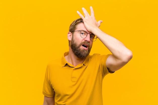 Giovane uomo biondo alzando il palmo alla fronte pensando oops, dopo aver fatto uno stupido errore