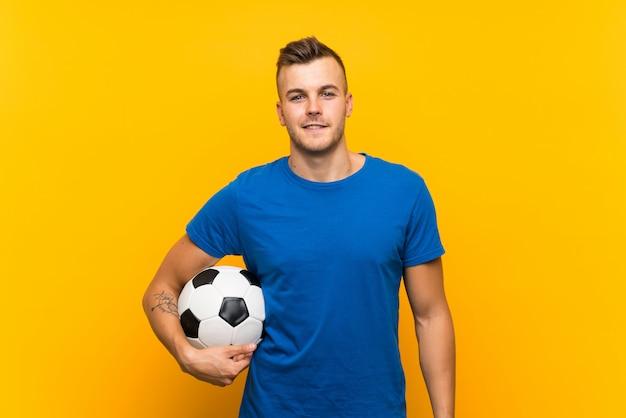 Giovane uomo biondo bello che tiene un pallone da calcio sopra la parete gialla isolata