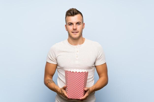 Giovane uomo biondo bello che tiene una ciotola di popcorn