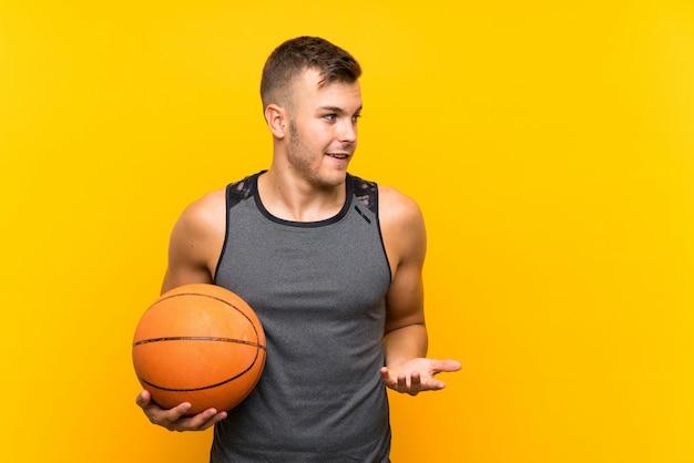 Giovane uomo biondo bello che tiene una palla del canestro con espressione facciale di sorpresa