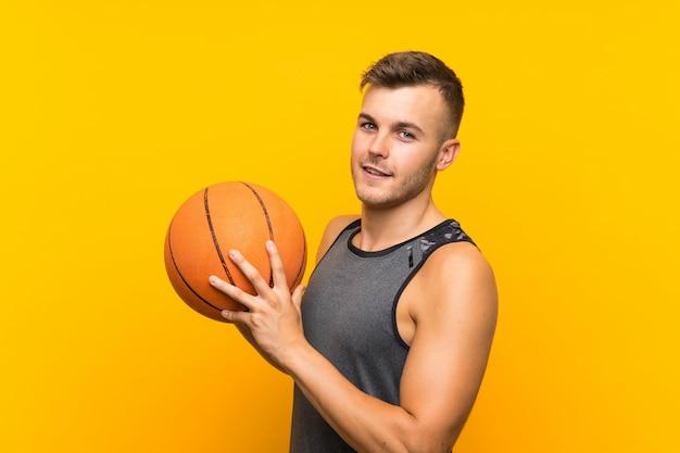 Giovane uomo biondo bello che tiene una palla del canestro sopra la parete gialla isolata