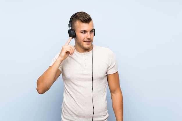 Giovane uomo biondo bello sopra fondo blu isolato che ascolta la musica con le cuffie
