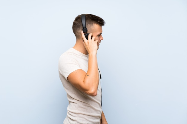 Giovane uomo biondo bello sopra la parete blu isolata che ascolta la musica con le cuffie