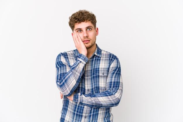 Giovane uomo biondo capelli ricci che è annoiato, affaticato e ha bisogno di una giornata di relax