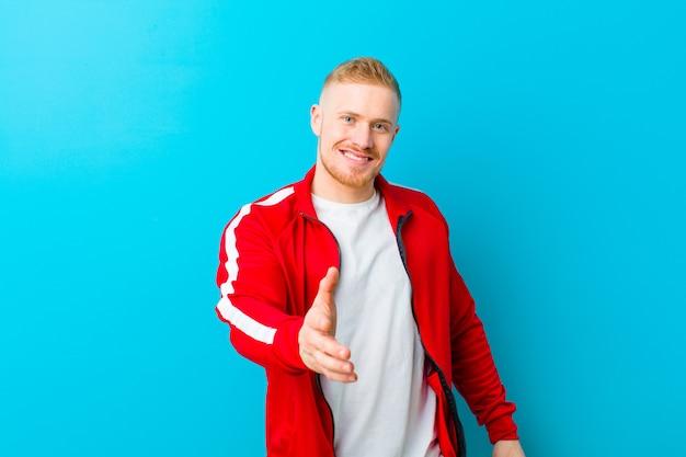 Giovane uomo biondo che indossa abiti sportivi sorridenti, guardando felice, fiducioso e amichevole, offrendo una stretta di mano per chiudere un affare, collaborando