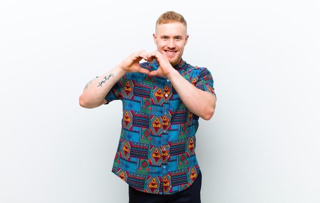 Giovane uomo biondo che indossa una camicia fresca sorridente e sentirsi felice, carino, romantico e innamorato, facendo a forma di cuore con entrambe le mani contro il muro bianco