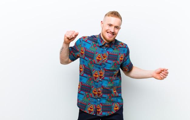 Giovane uomo biondo che indossa una camicia fresca sorridente, sentirsi spensierato, rilassato e felice, ballare e ascoltare musica, divertirsi a una festa su bianco