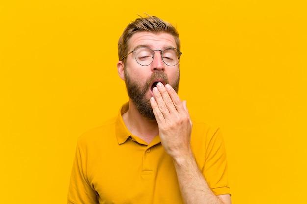 Giovane uomo biondo che sbadiglia pigramente nelle prime ore del mattino