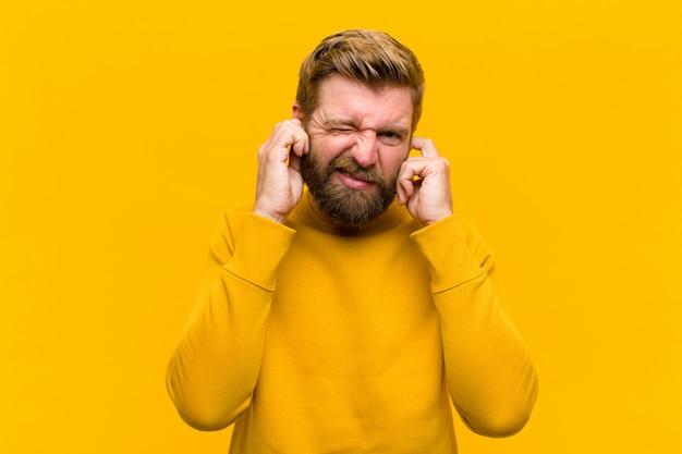 Giovane uomo biondo che sembra arrabbiato stressato e infastidito coprendo entrambe le orecchie per un suono assordante o musica ad alto volume