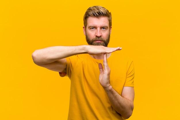 Giovane uomo biondo che sembra serio, severo, arrabbiato e dispiaciuto, rendendo il timeout firmare la parete arancione