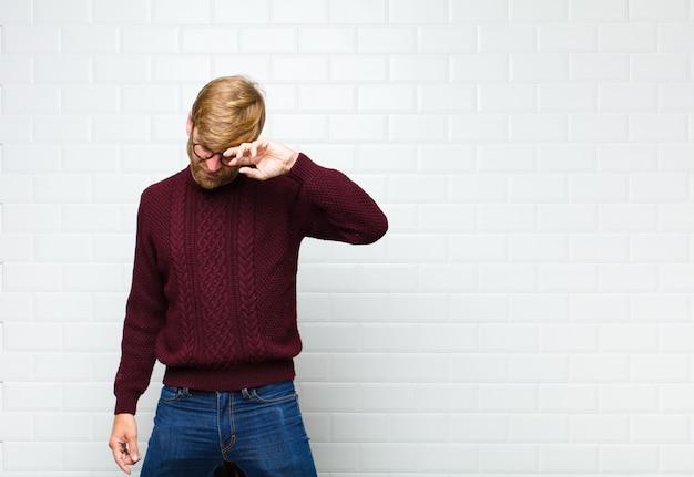 Giovane uomo biondo che sembra stressato, stanco e frustrato, asciugando il sudore dalla fronte, sentendosi disperato ed esausto muro di piastrelle vintage agaist