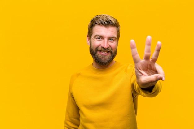 Giovane uomo biondo che sorride e che sembra amichevole, mostrando numero tre o terzo con la mano in avanti, contando la parete arancione