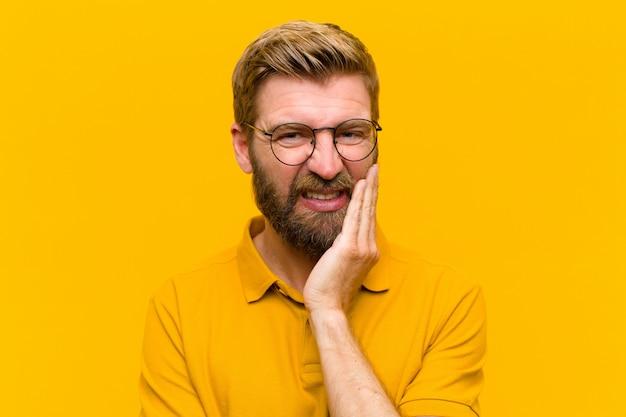 Giovane uomo biondo che tiene la guancia e soffre di mal di denti doloroso, sentirsi male, miserabile e infelice, in cerca di un dentista contro il muro arancione