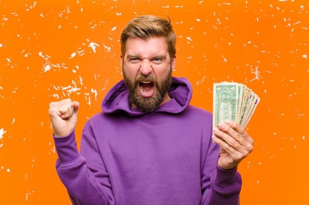 Giovane uomo biondo con le banconote in dollari o le banconote che indossano una maglia con cappuccio porpora contro la parete arancio danneggiata