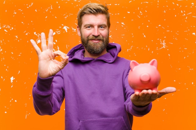 Giovane uomo biondo con un salvadanaio che indossa una felpa con cappuccio viola contro il muro arancione danneggiato