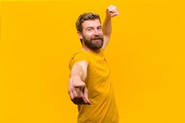 Giovane uomo biondo sentirsi felice e fiducioso, indicando la fotocamera con entrambe le mani e ridendo, scegliendo te contro il muro arancione