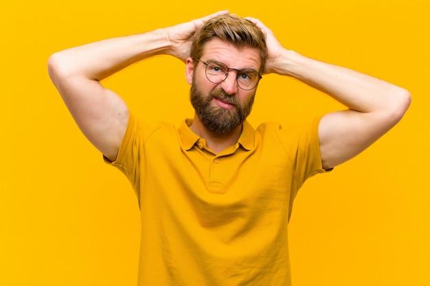 Giovane uomo biondo sentirsi frustrato e infastidito, malato e stanco del fallimento, stufo di noiosi, noiosi compiti muro arancione